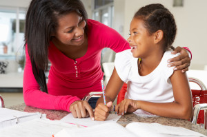 Mother Helping Daughter With Homework In Kitchen